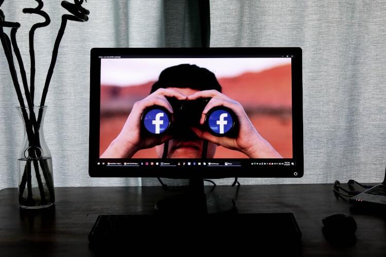 Tela do computador mostrando um binóculo com o logo do Facebook.