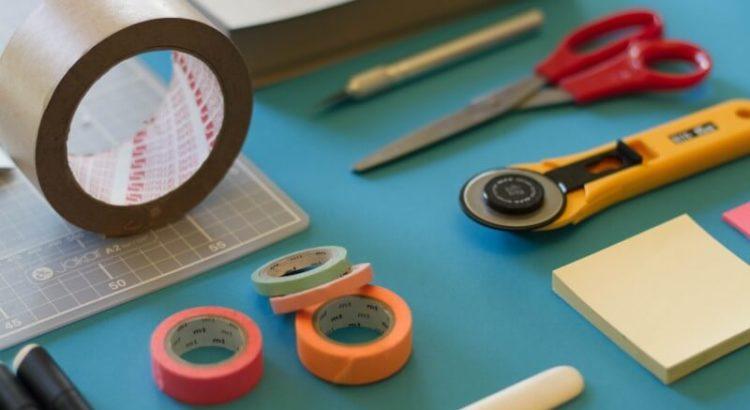 Mesa com materiais de escritório: fita adesiva, tesoura, estilete, entre outros.