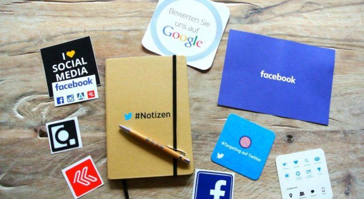 Mesa com vários adesivos de redes sociais.