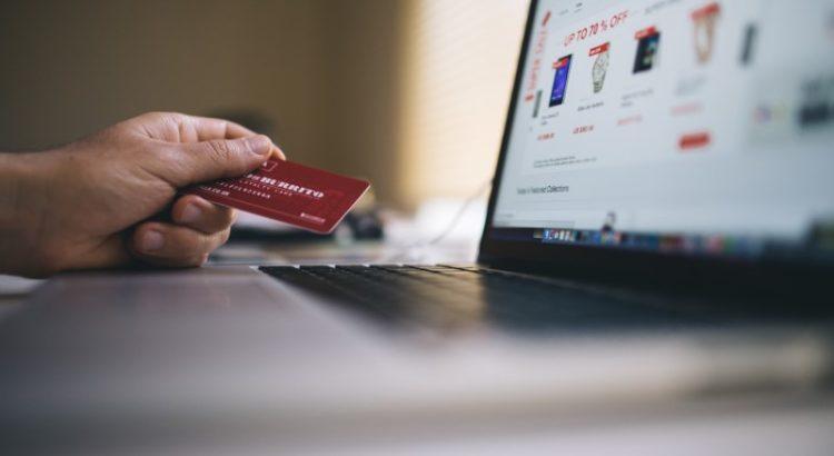 Pessoa segurando cartão de crédito em frente ao PC.