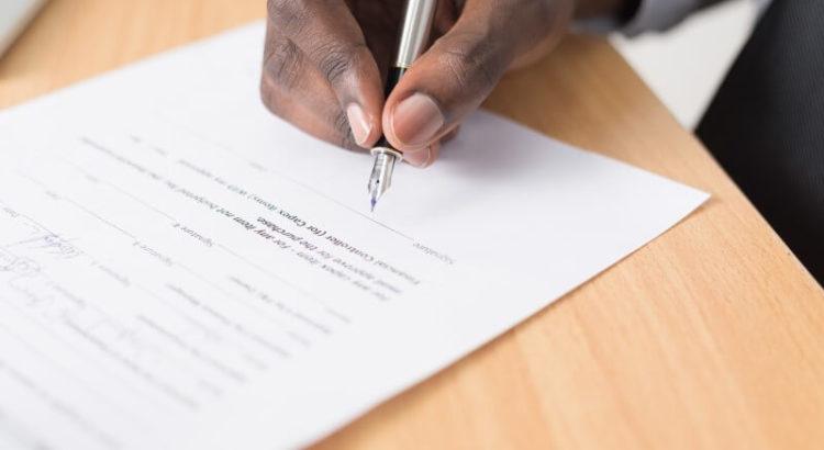Pessoa assinando documentos.
