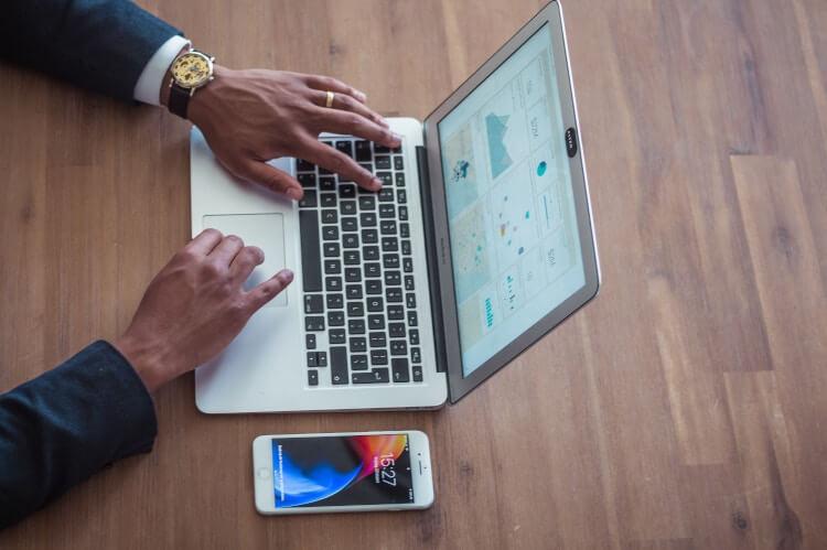 Pessoa pesquisando preços de produtos em um laptop.