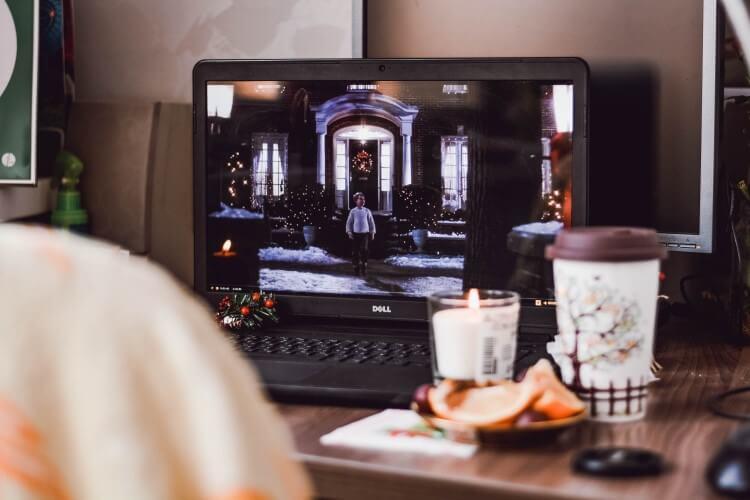 Mesa de trabalho no estilo home office, com notebook, café e comida.