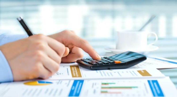 Pessoa fazendo contabilidade com papéis de calculadora.