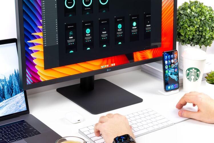 Mesa de trabalho com tela, teclado, notebook, celular e café.