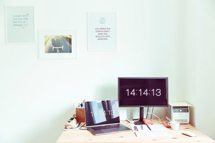 Mesa de trabalho com tela de computador, notebook e outros itens.