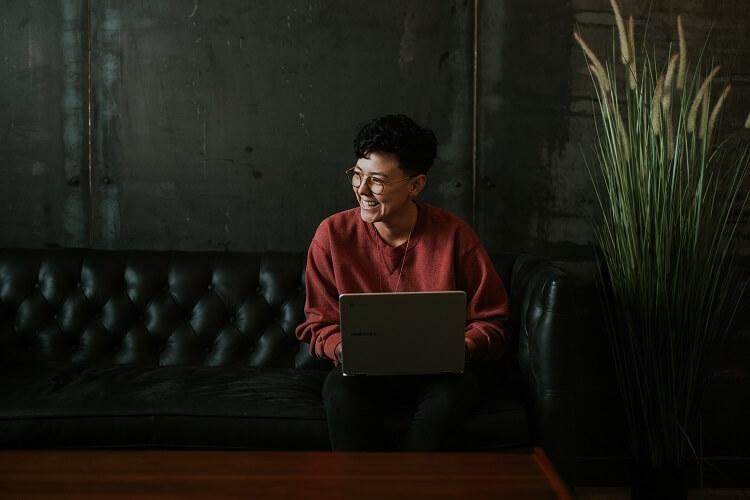 Mulher sentada no sofá com notebook no colo.