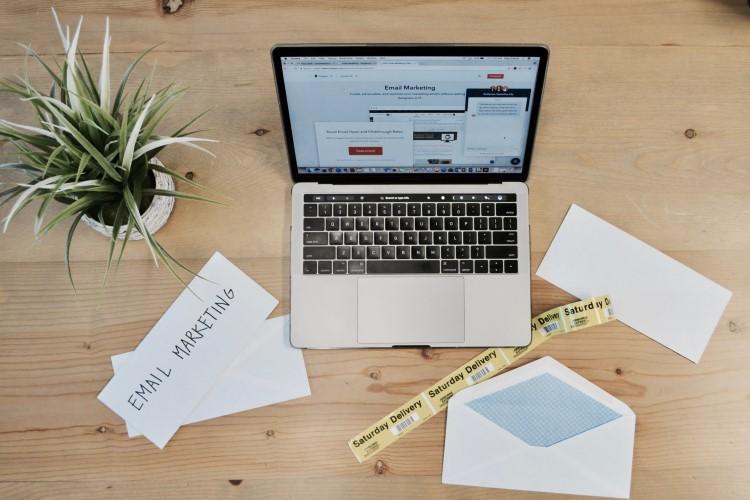 Notebook e papéis sobre uma mesa, com anotações de marketing.
