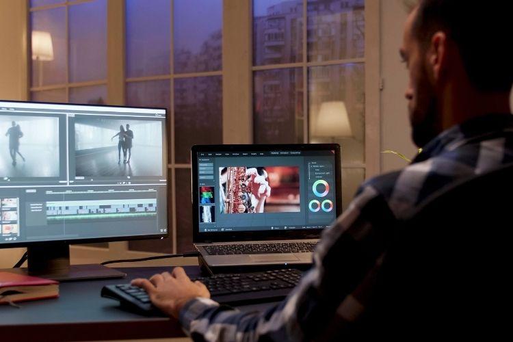 Homem na frente de dois computadores editando vídeos.